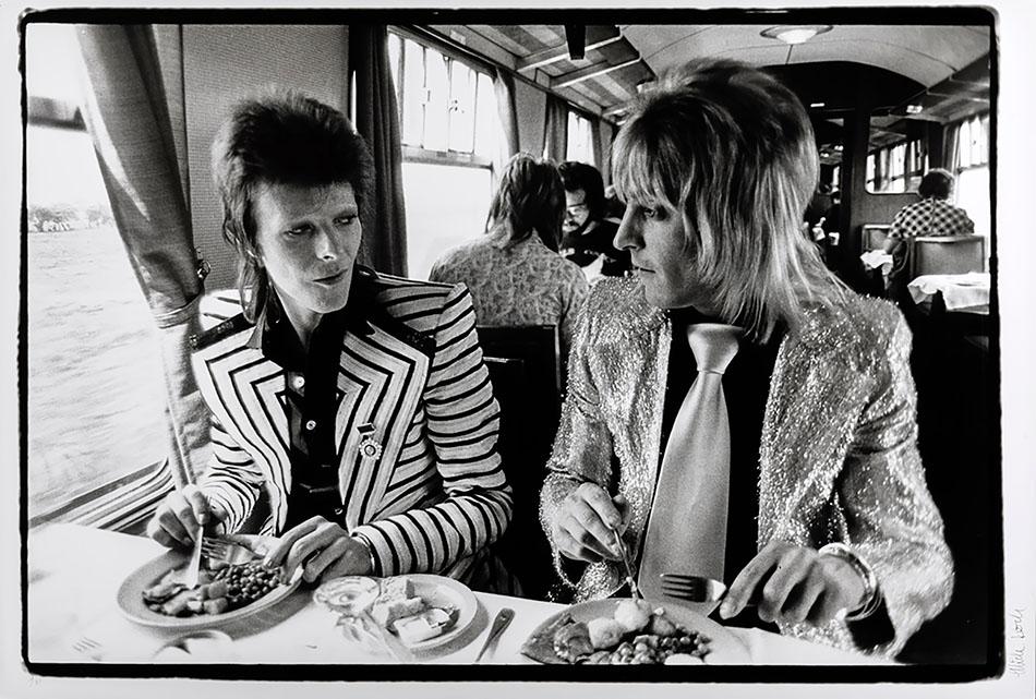 Fotografen Mick Rock har foreviget David Bowie og Mick Ronson idet de spiser lunsj på toget til Aberdeen i 1973. Fotografiet tilhører Møllersamlingen.